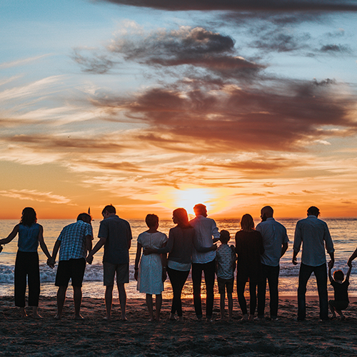 Gathering of 11 people of all ages, watching the sunset at the beach