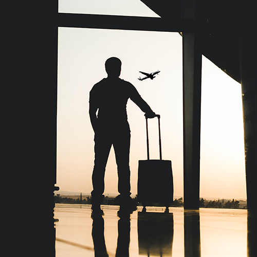 Silhouette of person with suitcase watching an airplane taking off from an airport